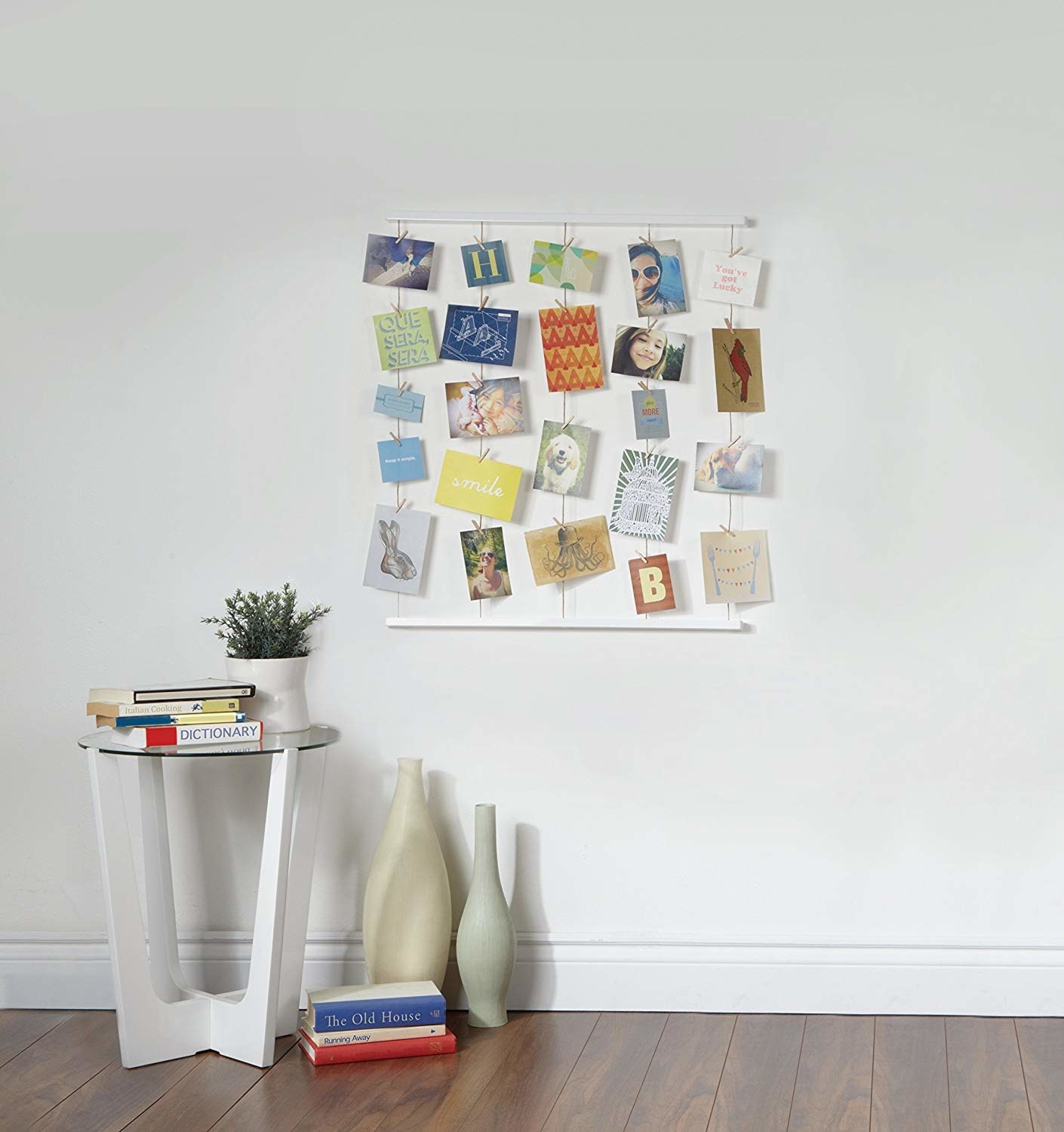 A bunch of photos clipped to a set of strings on the wall
