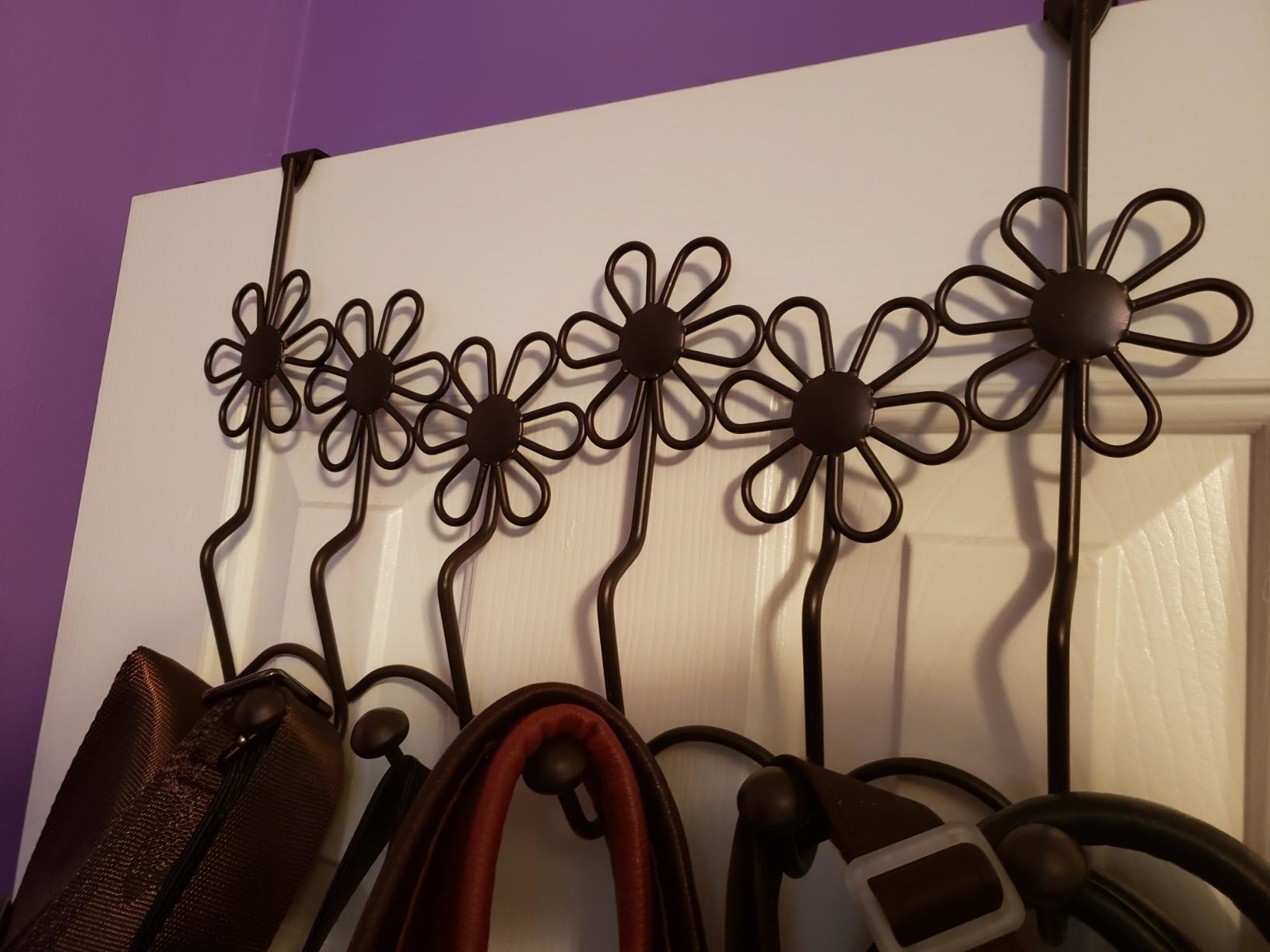 The floral design rack with hooks holding up some items