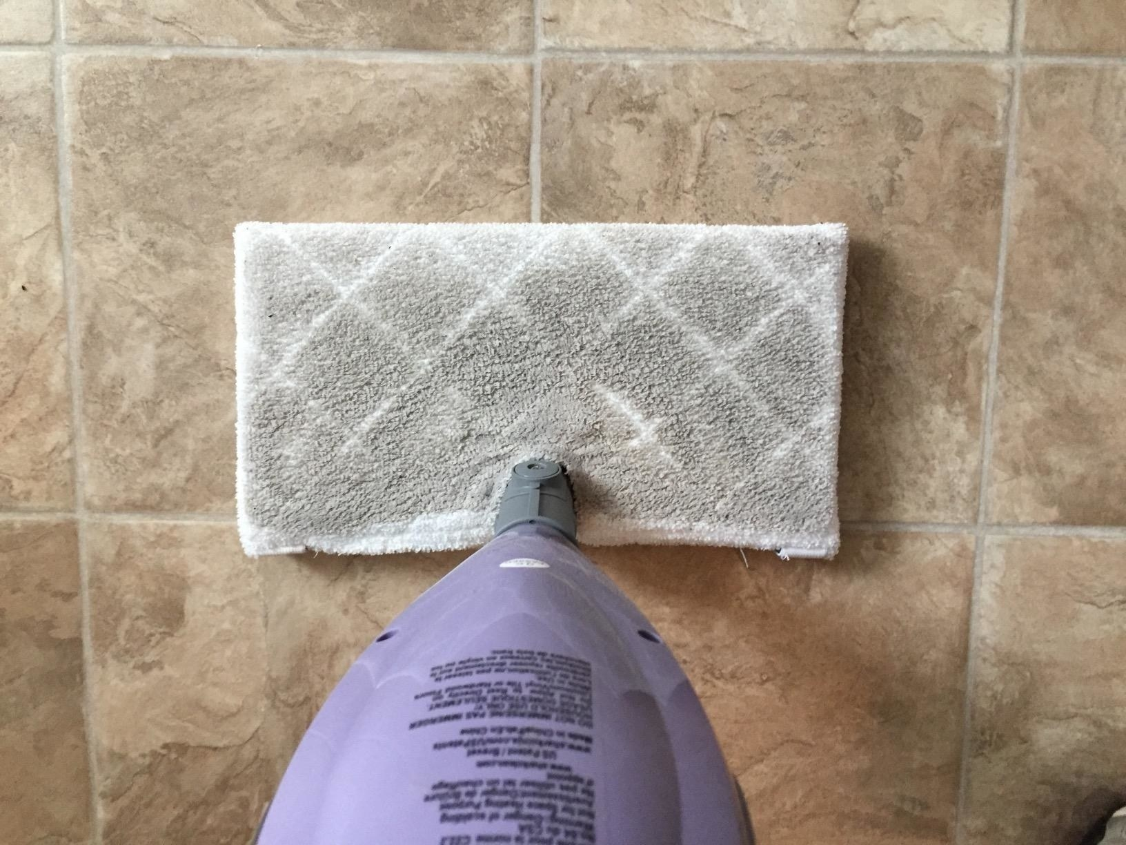 A reviewer's dirty mop head on their tile floor