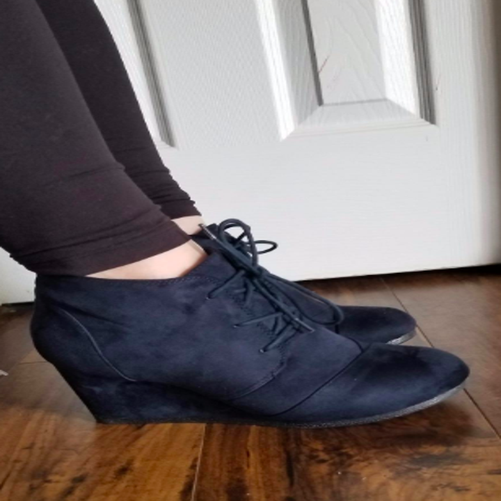 A reviewer wearing the faux-suede booties in navy