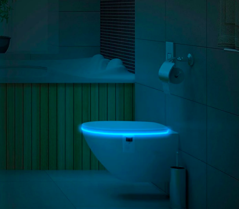Closed toilet seat glowing from the inside in a dark bathroom