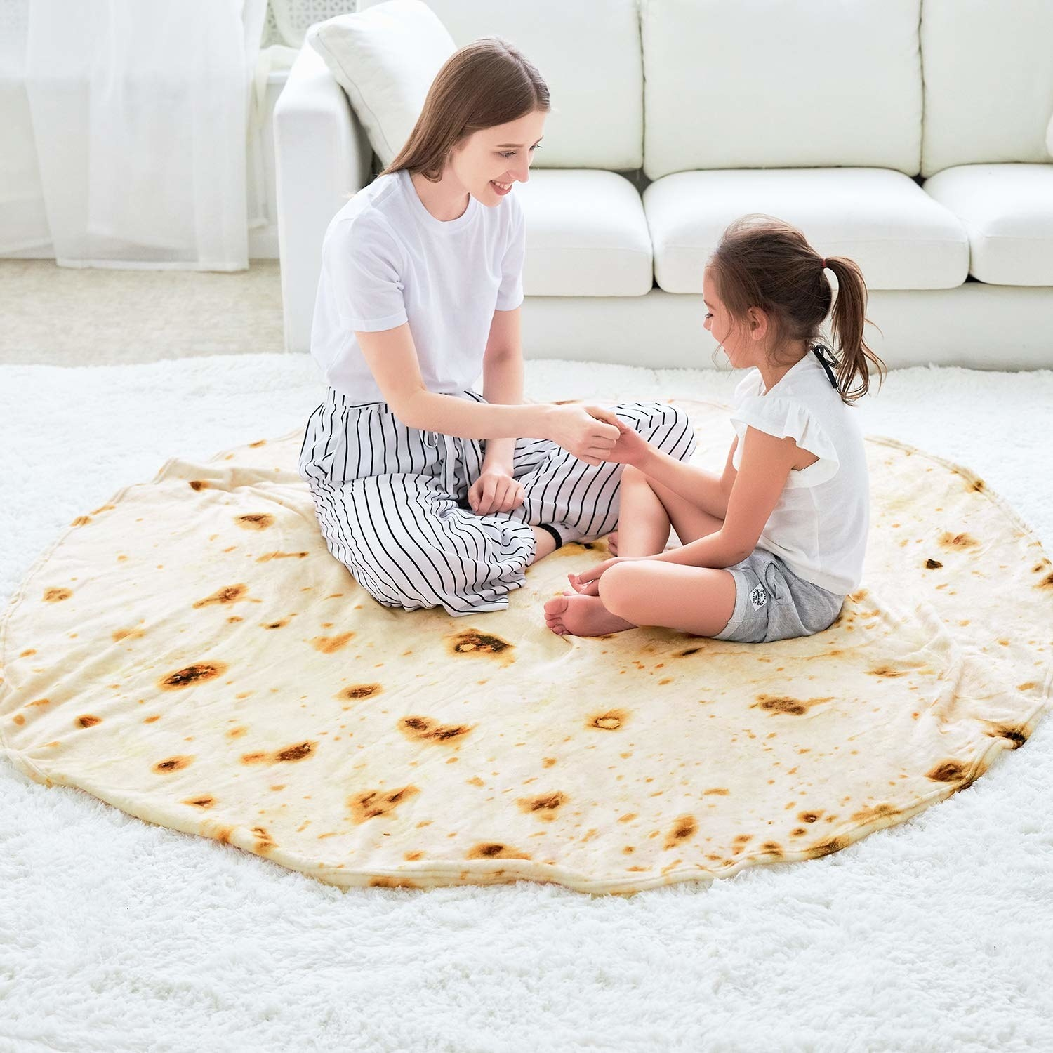 Two people sitting on round tortilla blanket