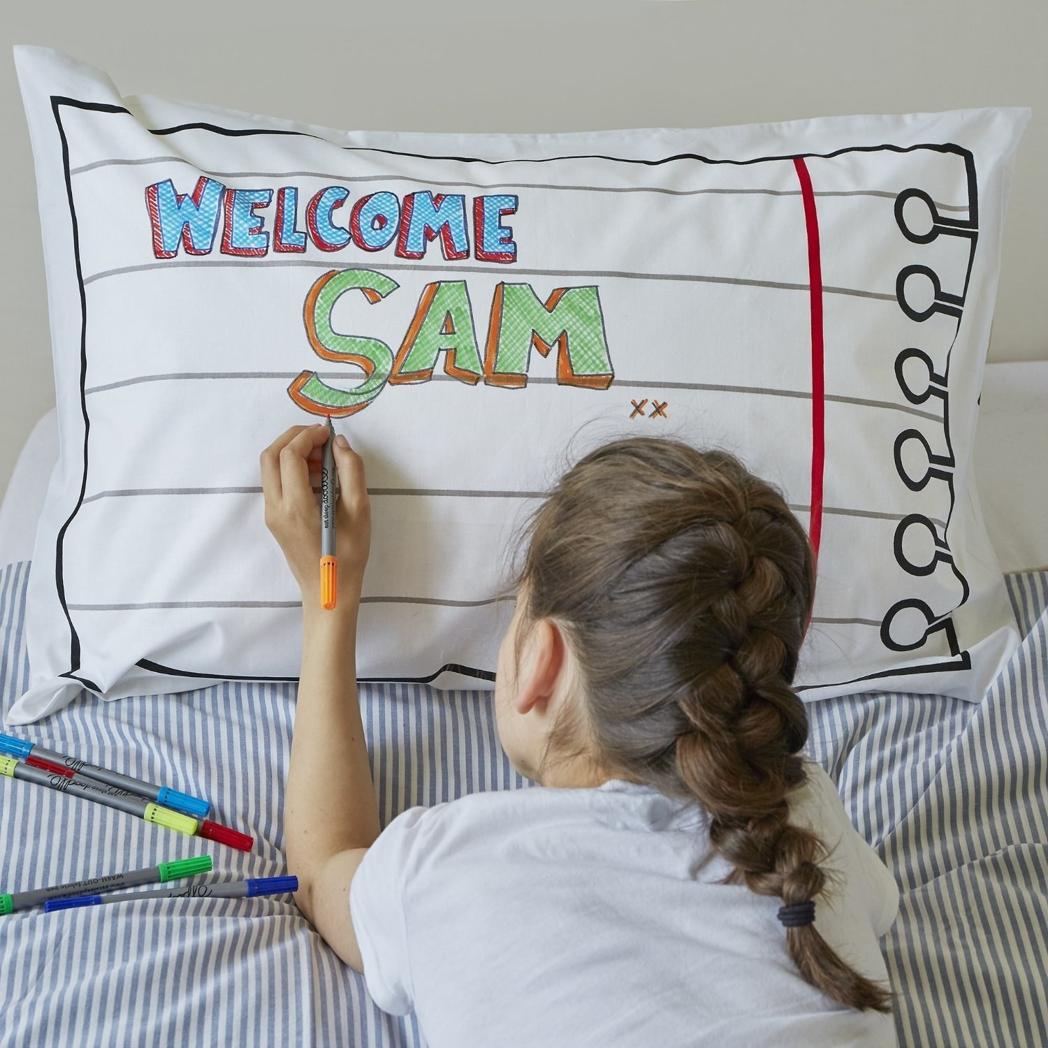Child drawing on pillowcase that looks like piece of torn notebook paper