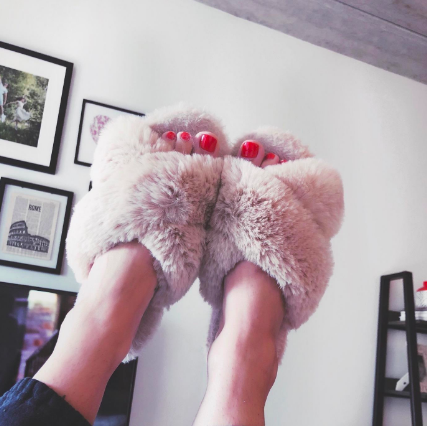 Reviewer holding feet up in fluffy open-toed slippers
