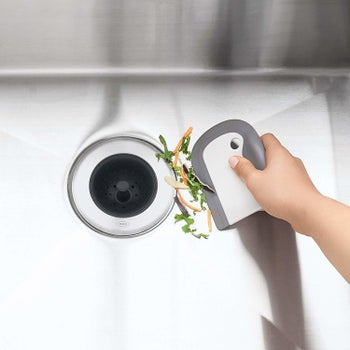 A hand using it to push scraps down a garbage disposal