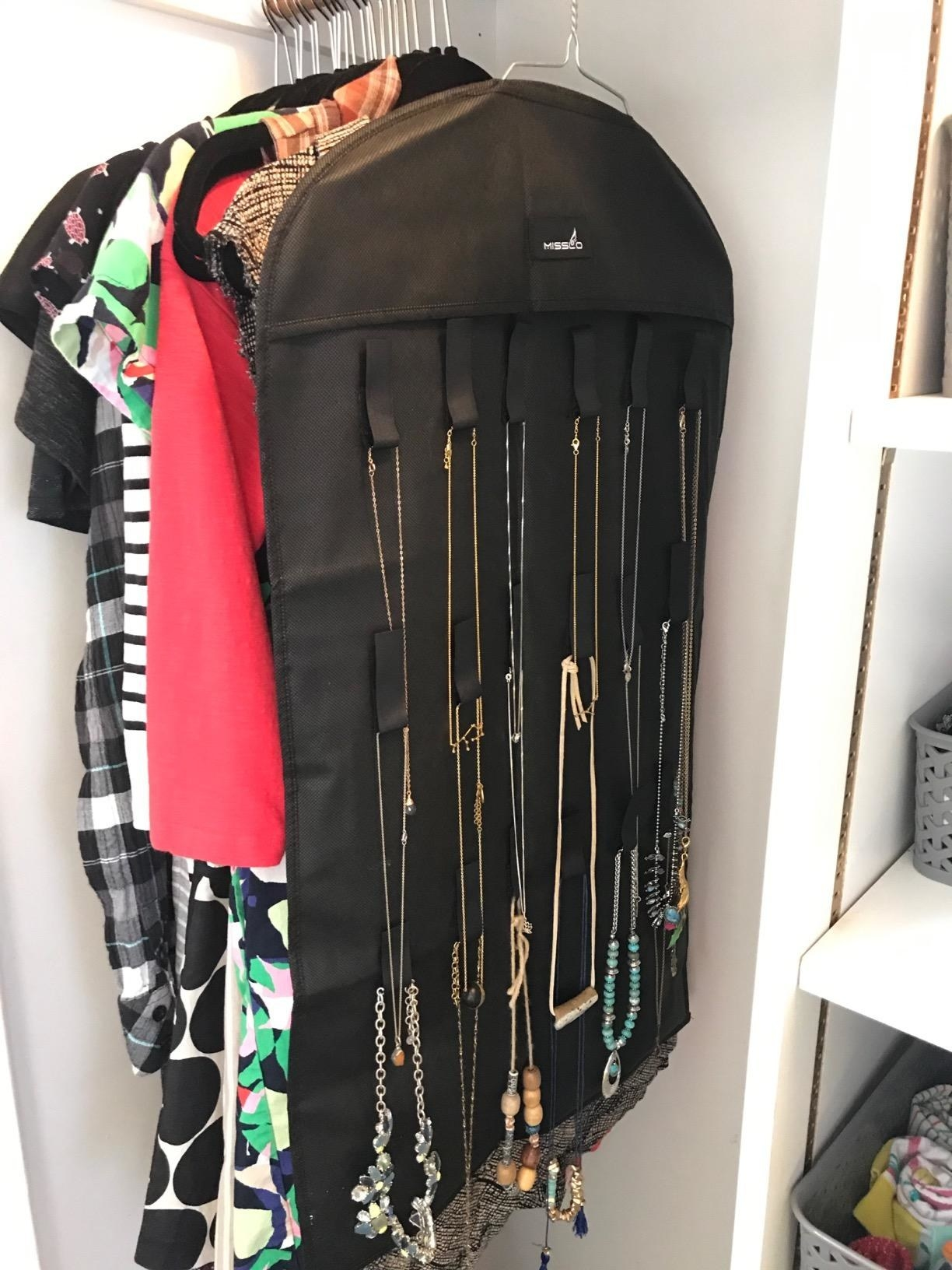 A reviewer showing the rack with necklaces hanging in their closet with their clothes