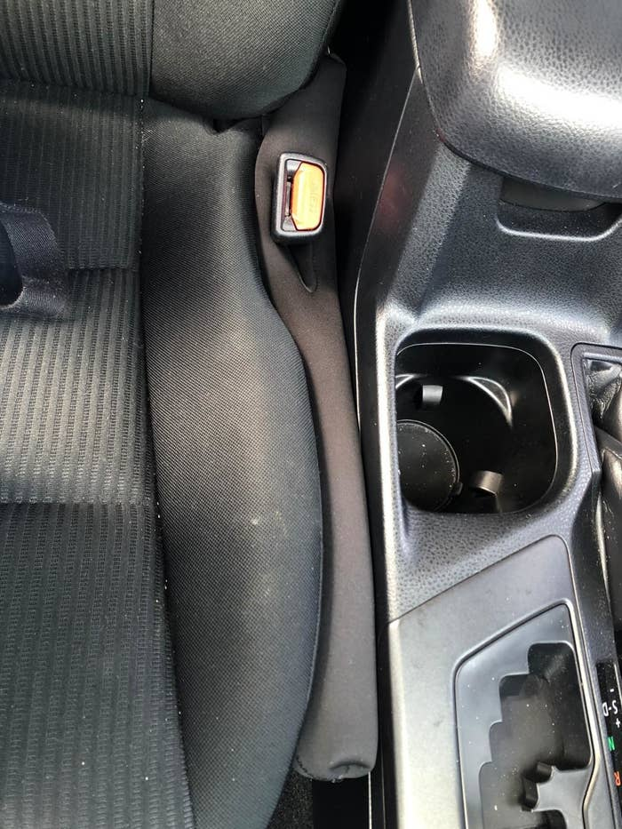 reviewer's drop stop squished between their passenger seat and cup holder