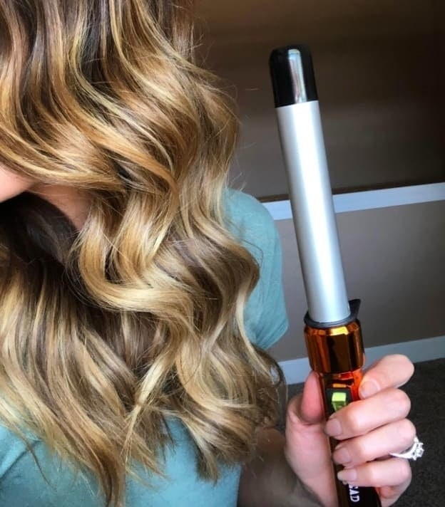 reviewer with loose curls holding the curling wand
