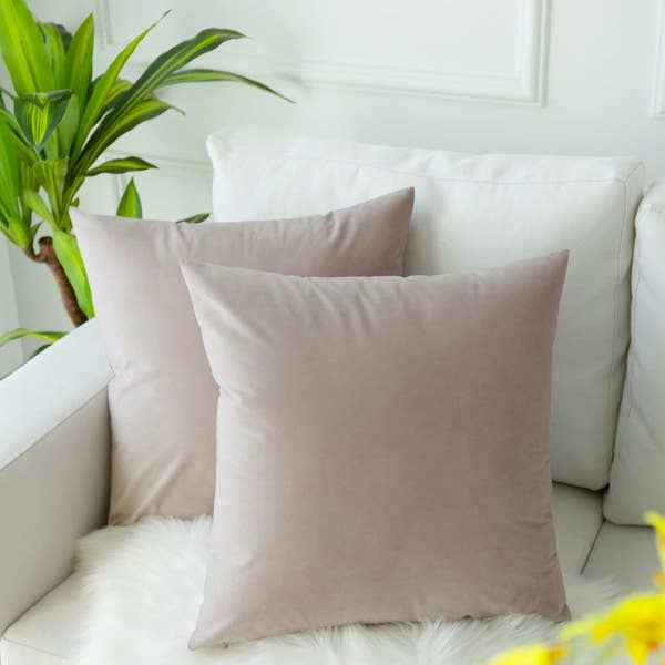 Two light pink velvet pillowcases on a couch
