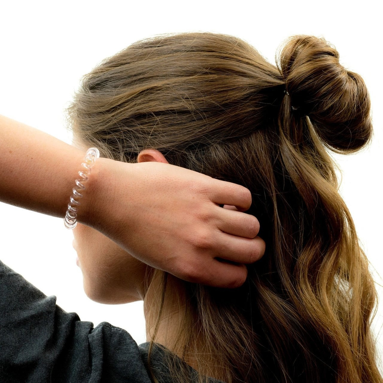 Model with with her hair half up and a clear spiral hair tie around her wrist
