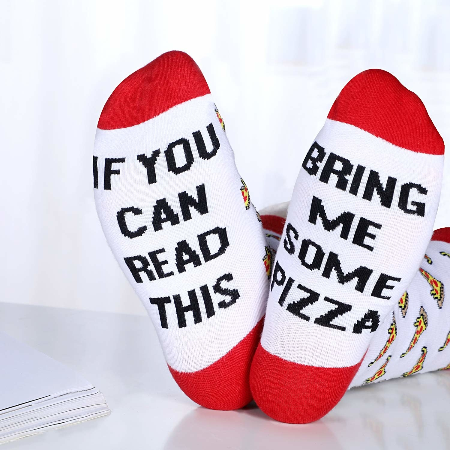 "Red and white socks printed with pizza slices and with the text ""If you can read this"" on on the bottom of one foot and ""Bring me some pizza"" on the bottom of the other"