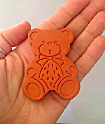 A hand holding the terracotta bear