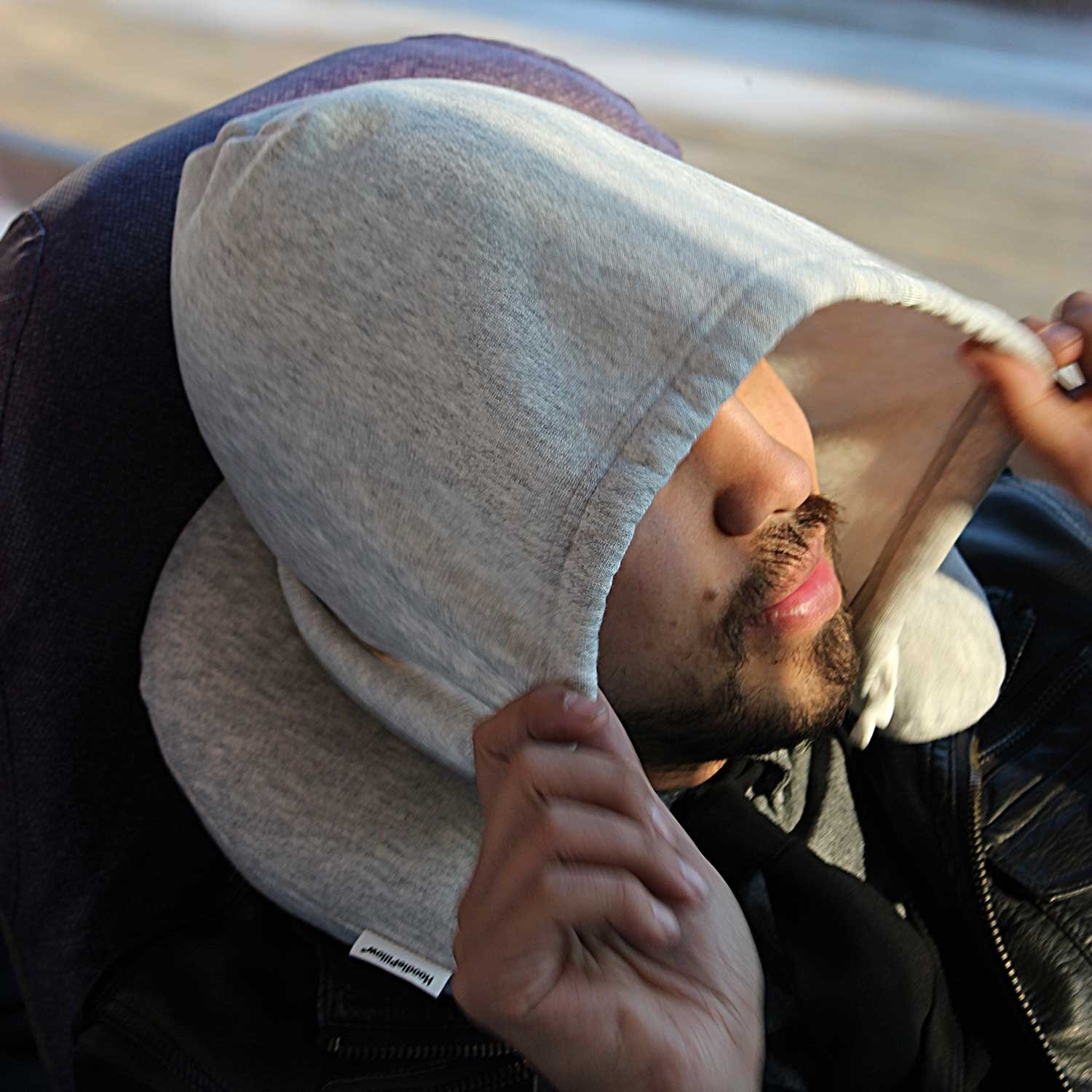 A model using the pillow in grey with the hood up
