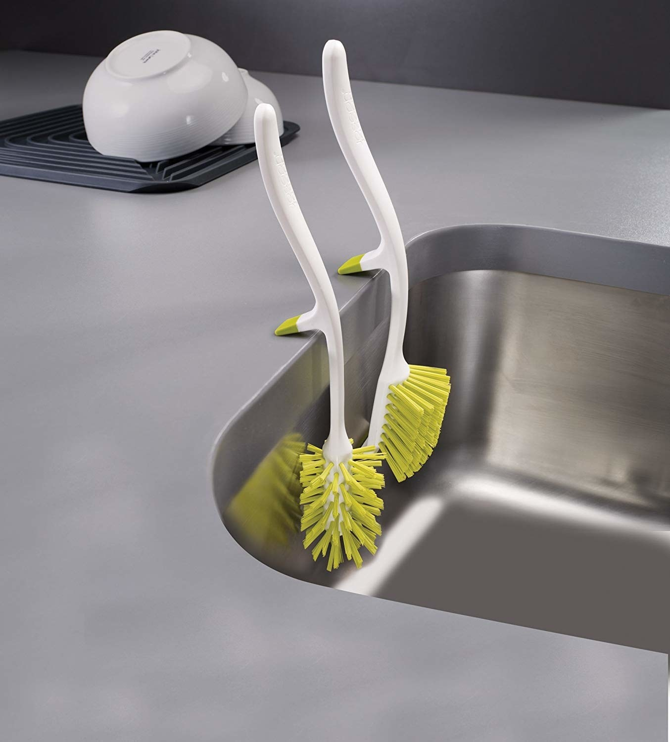 Two brushes hanging from side of sink