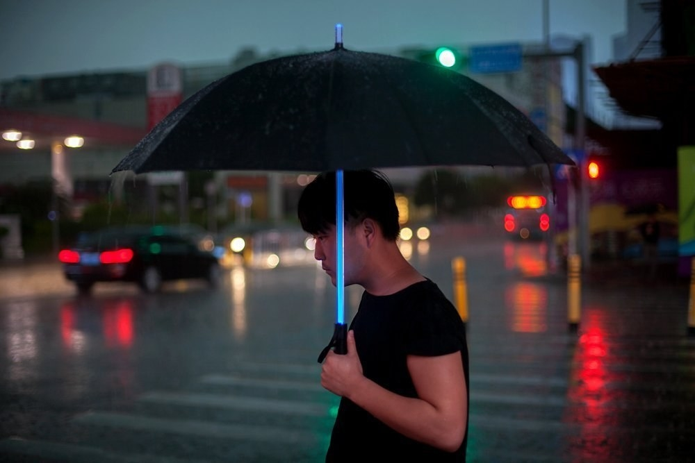 A lifestyle image of a person walking on a rainy street with the pole of their black umbrella shining blue