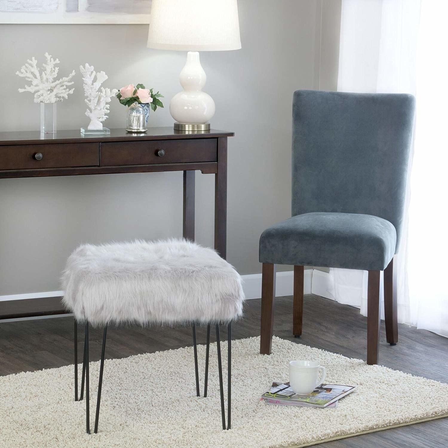 The ottoman with metal peg legs and a fuax fur top in a living room