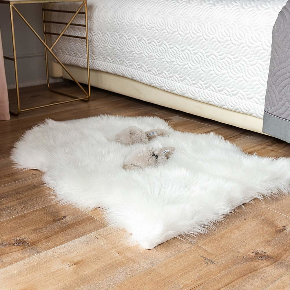 The small white faux sheepskin rug on the floor next to a bed with slippers on it