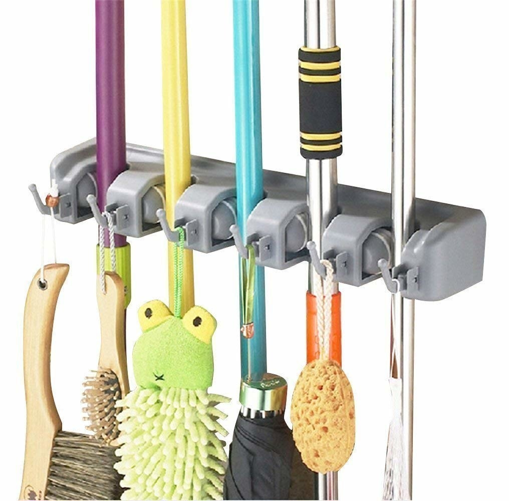 A rectangular rack with five slots holding cleaning supplies like brooms and mops There are small hooks holding a brush, sponge, and umbrella