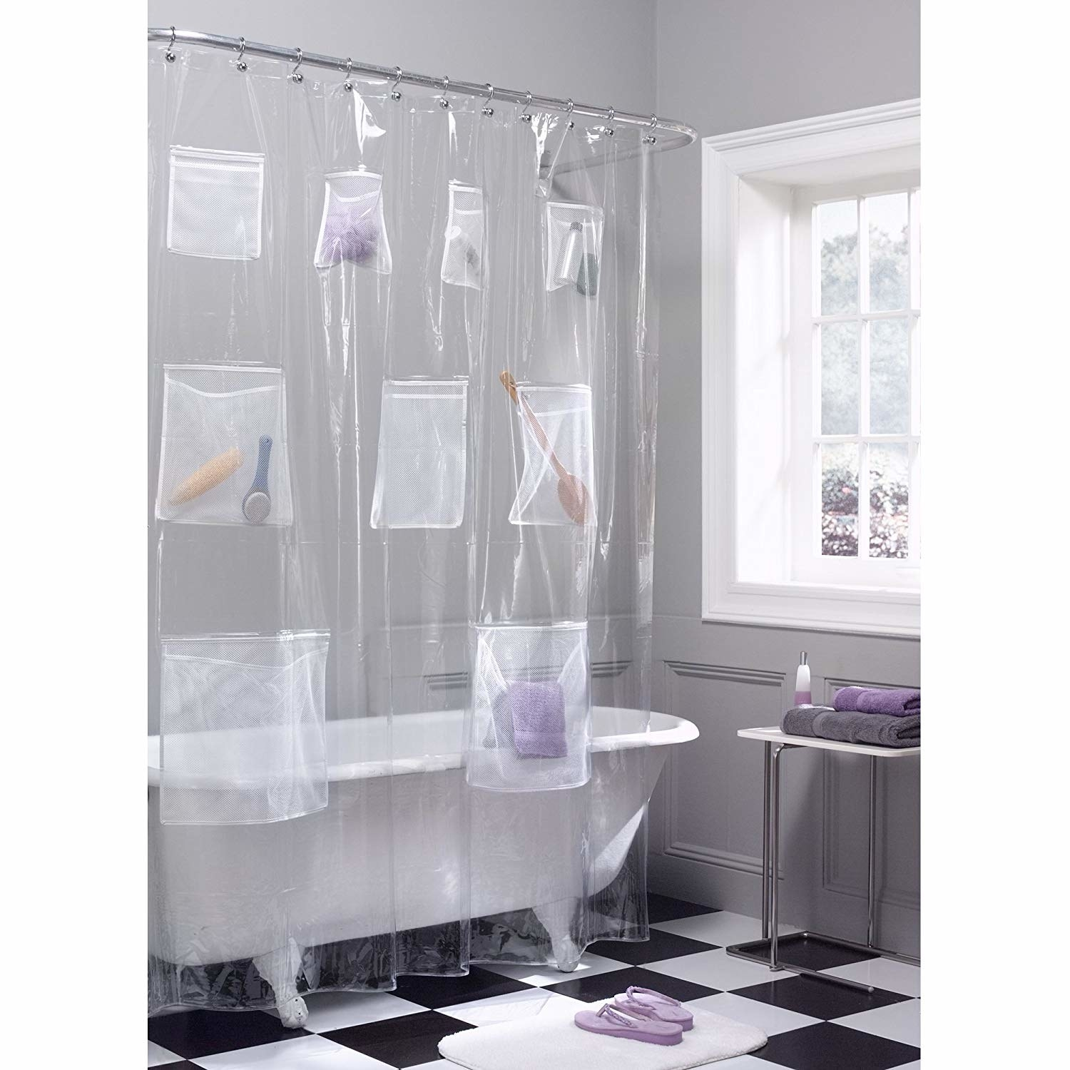 A plastic shower curtain with nine pockets on it The pockets are different sizes and have different items like a loofah, beauty products or towels inside.