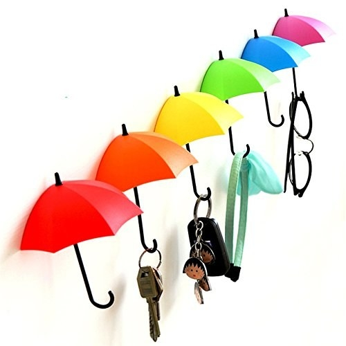 Umbrella hooks attached to a wall with keys, hair band, and glasses hanging on them.