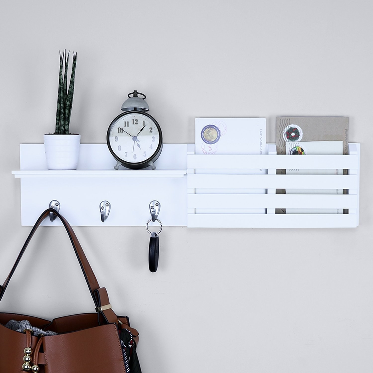 A shelf is mounted to a wall It has a small shelf, three hooks, and a letter slot