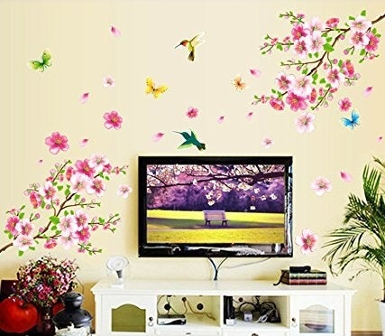 Floral wall decal pasted on a wall behind a TV and entertainment set-up.