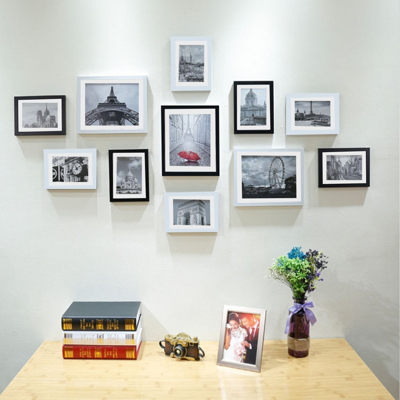 Photo frames hung on a wall with images of numerous landscapes, in front of a table.