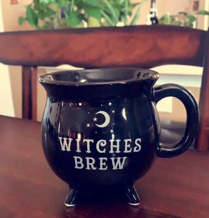 "a black mug shaped like a cauldron with four legs on the bottom and a handle. It says, ""witches brew."""