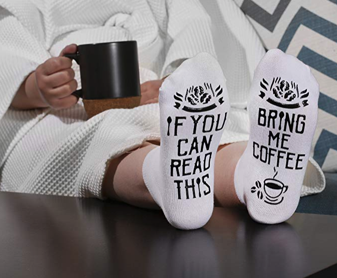 A person sitting with feet on a coffee table wearing socks that say if you can read this bring me coffee
