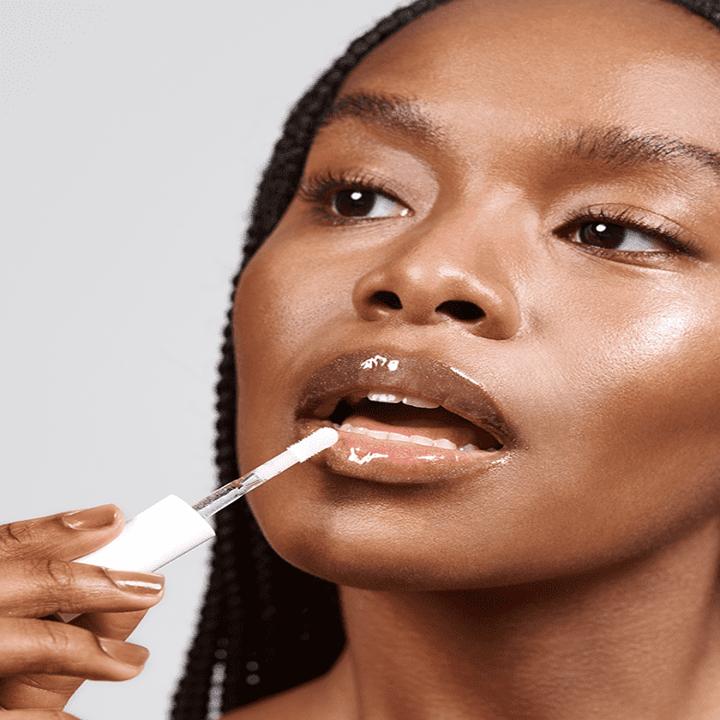 Person applying shiny lip gloss