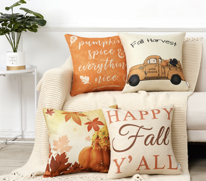 "four fall pillows. one is orange and says ""pumpkin spice and everything nice."" Another says, ""Fall Harvest"" and has a truck with fall produce on it. Another has pumpkins nad leaves on it. The last pillow says ""Happy Fall Y'all."""