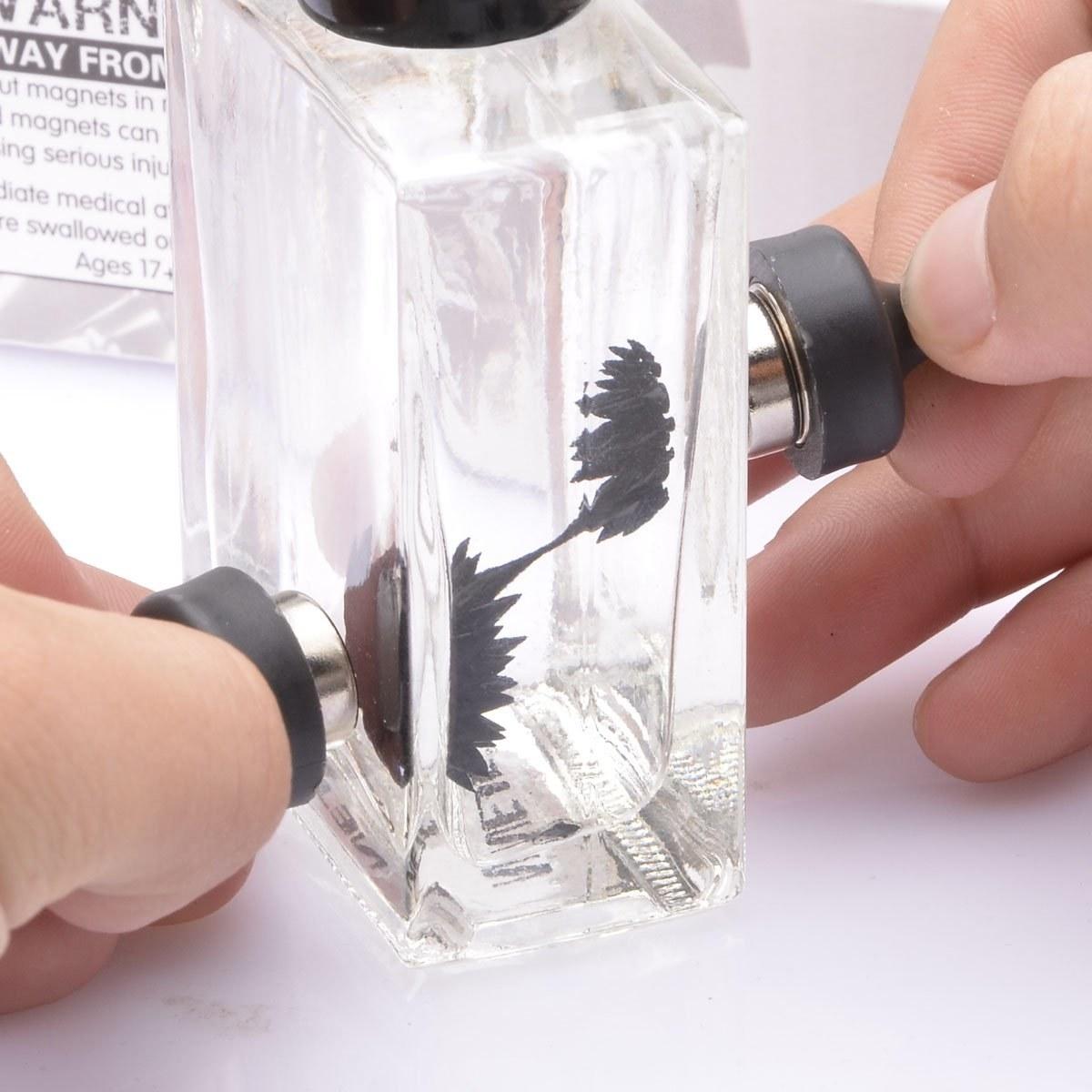 model uses magnets to make black liquid in glass bottle spiky