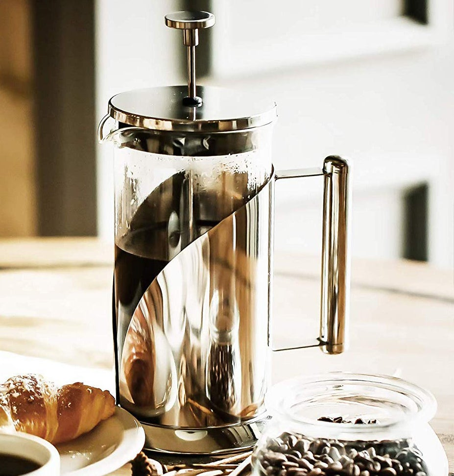 A metal French press on a table next to a glass jar full of coffee beans and a plate with a croissant on it