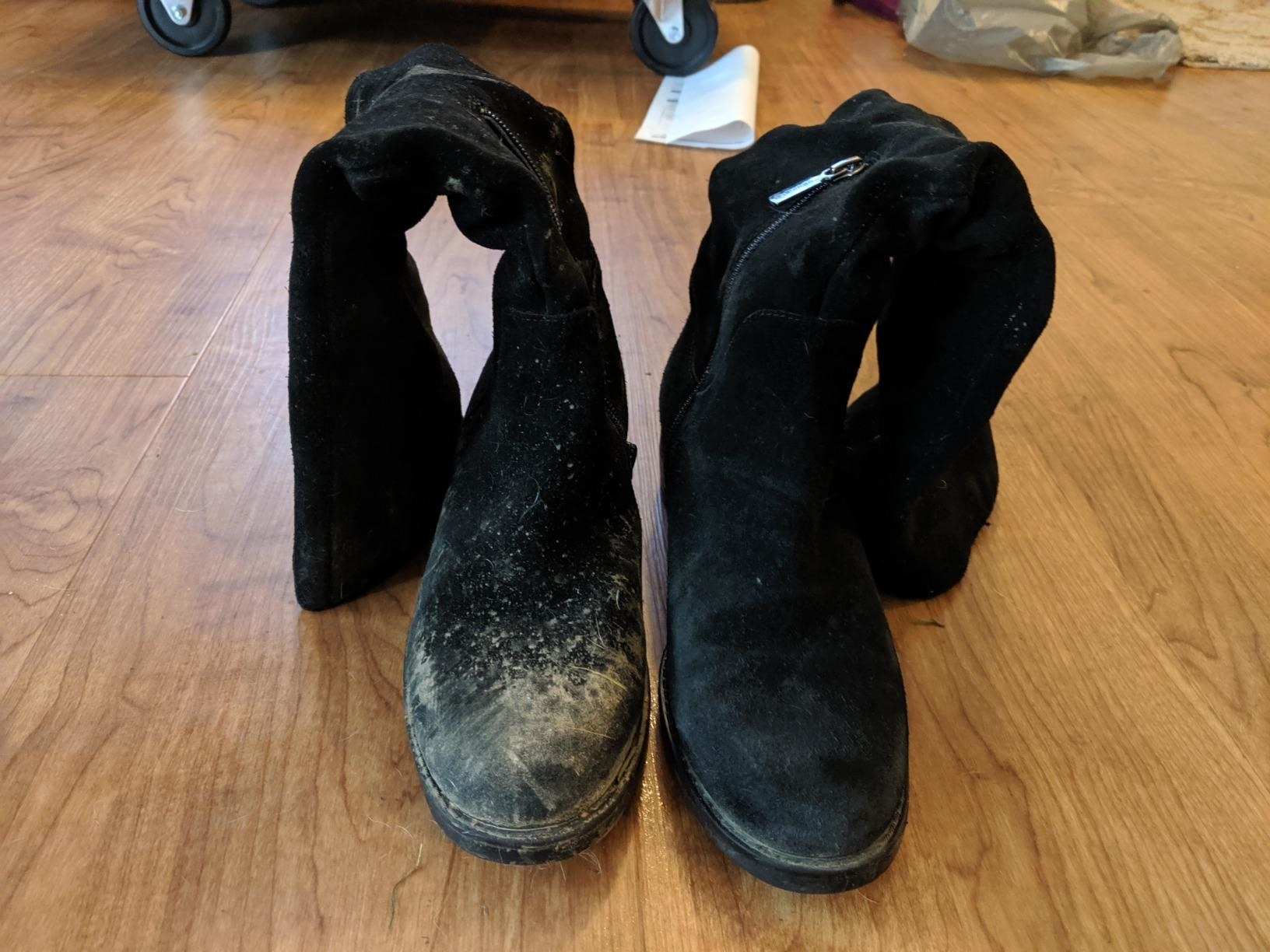 A reviewer's black suede boots: the left covered in light brown dirt, the right completely clean and new-looking