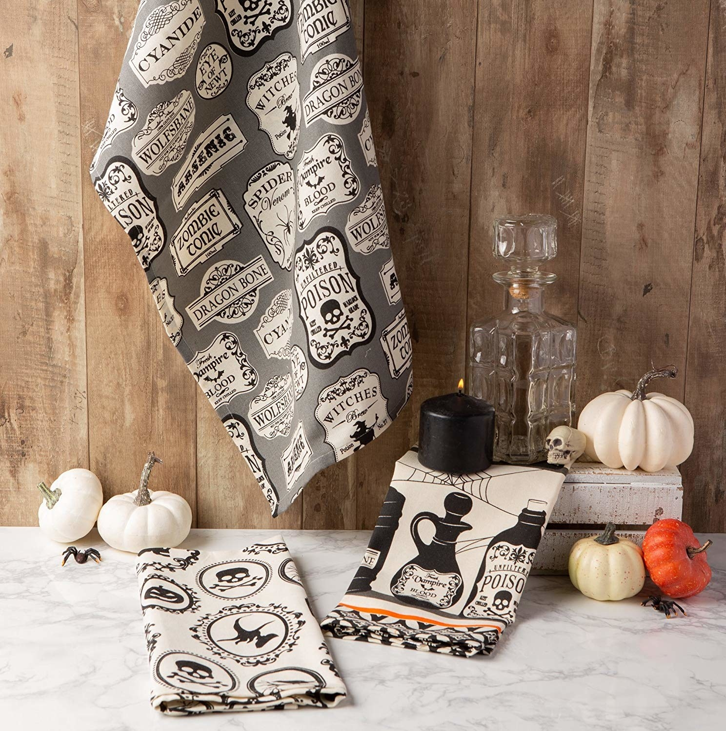 three tea towels with vintage style halloween patterns like poison labels and skulls