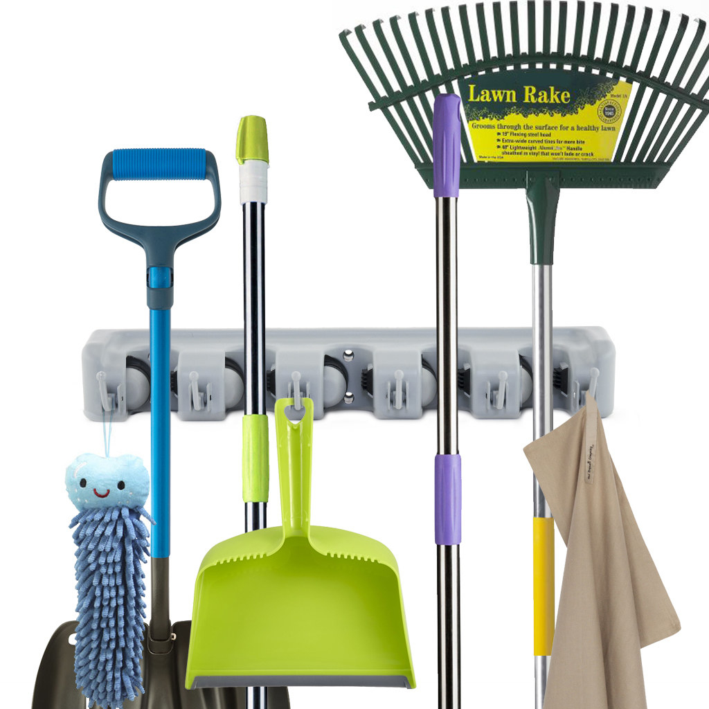 the wall-mounted rack holding a collection of cleaning tools
