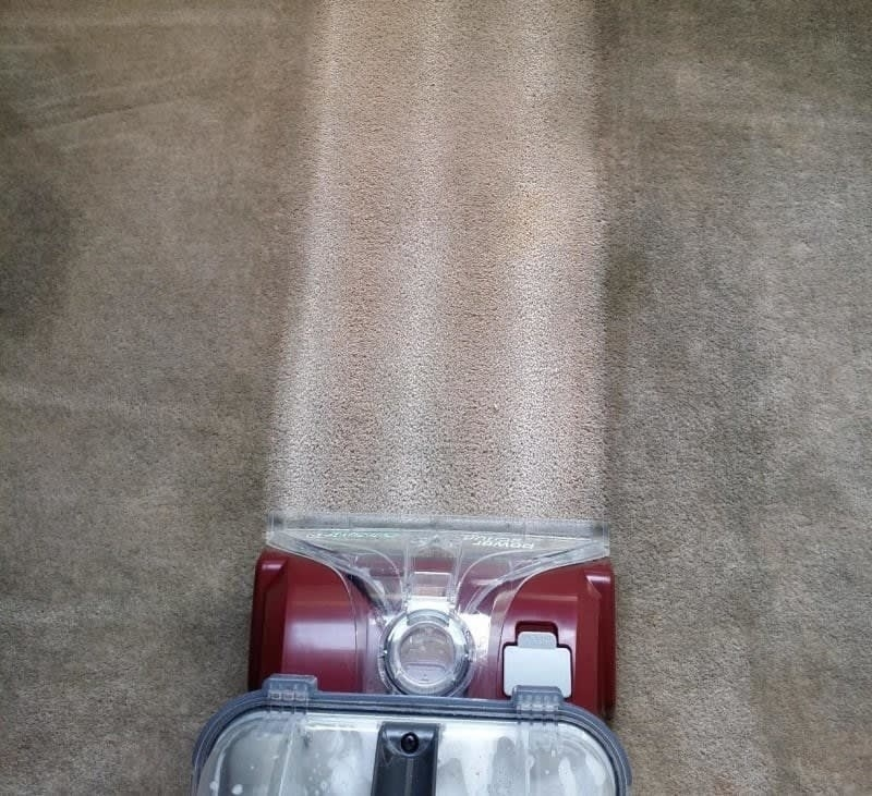 A reviewer running a carpet cleaner across a darkened, dirty carpet and the machine leaves a trail of clean carpet