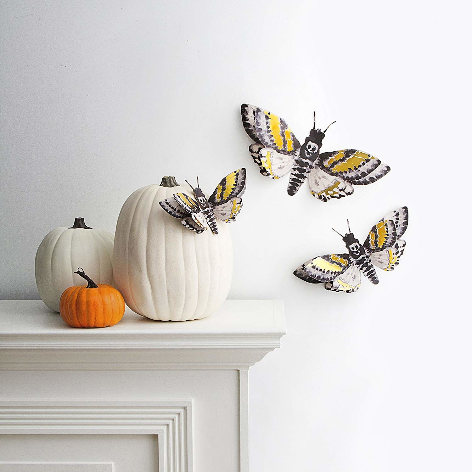 Three paper moths with gold detail and skull pattern