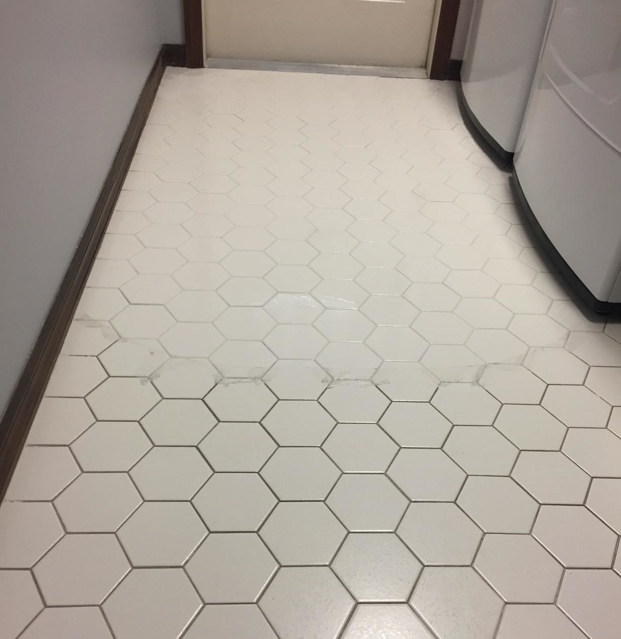 A tiled floor that has been scrubbed and now looks much brighter, whiter, and cleaner than the section of the floor that has not yet been scrubbed