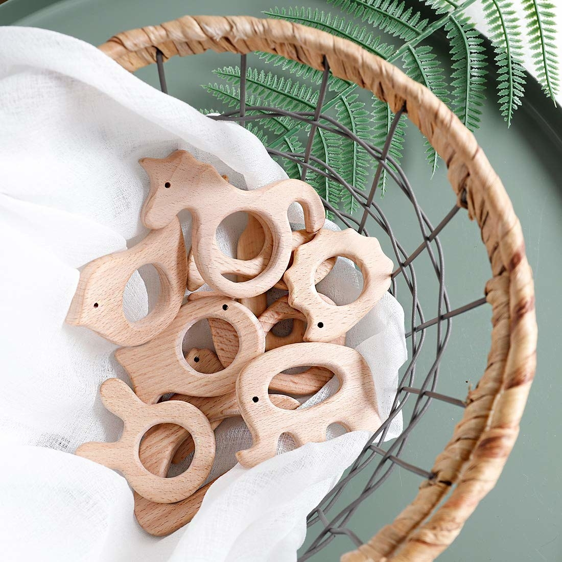 A basket filled with animal-shaped teethers made of natural wood