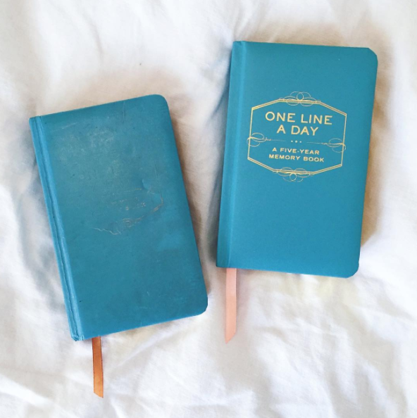 two one line a day memory books on a bed; the first is old and the second is new