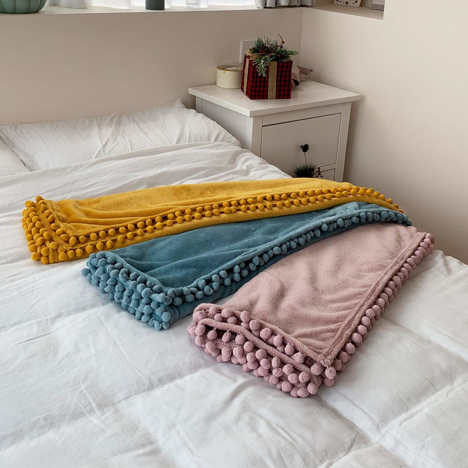 Three fuzzy blankets with pom poms down the sides across a white bedspread