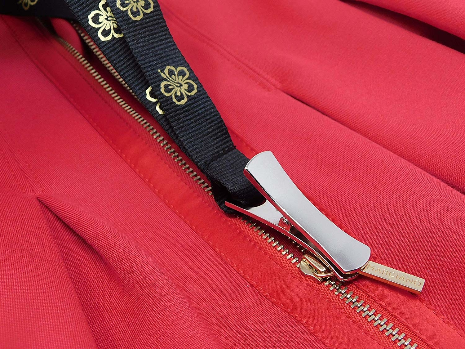 a zipper puller attached to a black zipper on a red top
