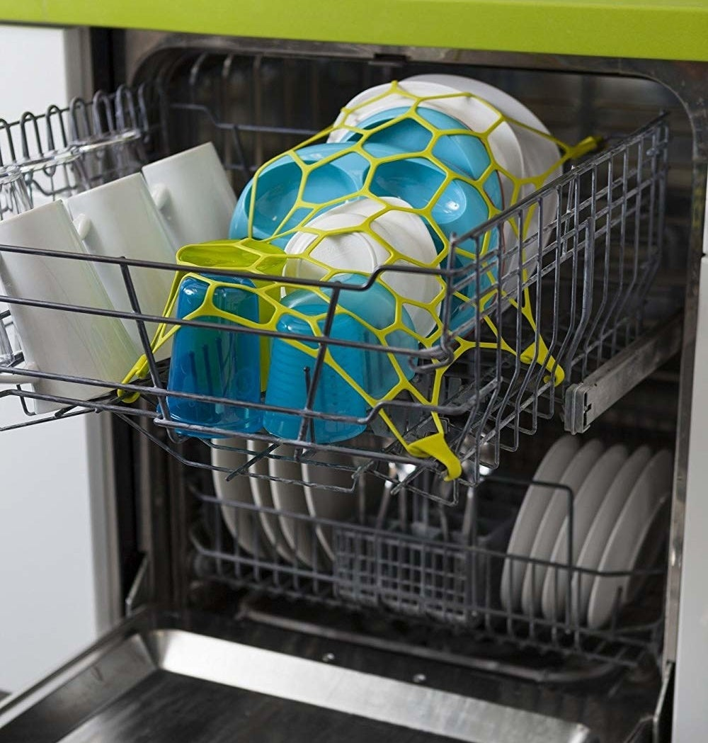 open washing machine with stretchy net on top of things in the top rack of dishwasher