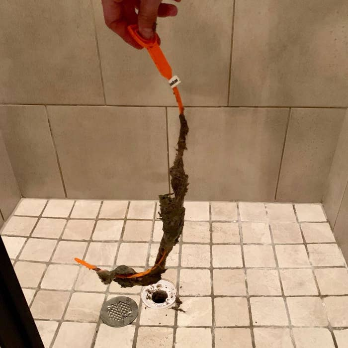a drain snake covered in grime and hair after being used to clean a shower drain
