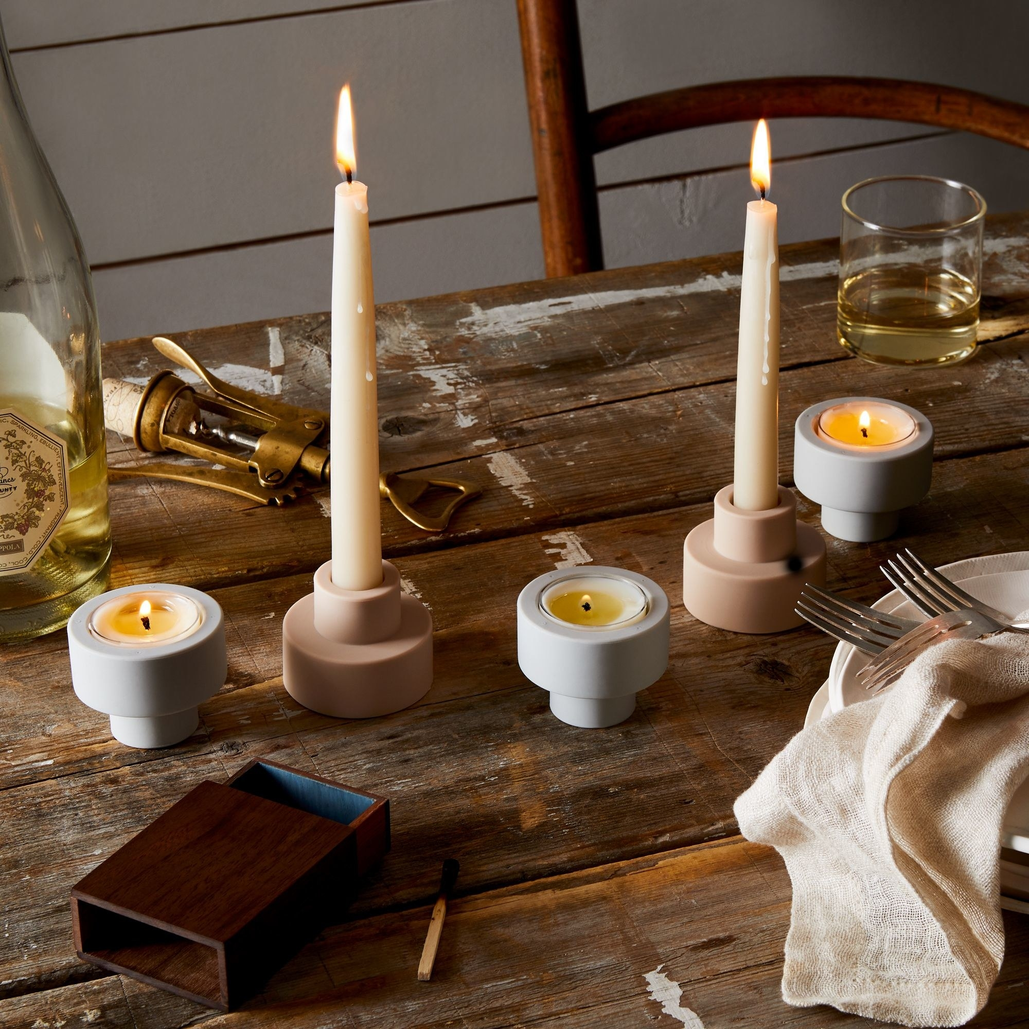 The candle holders on a table with tea lights and large candles