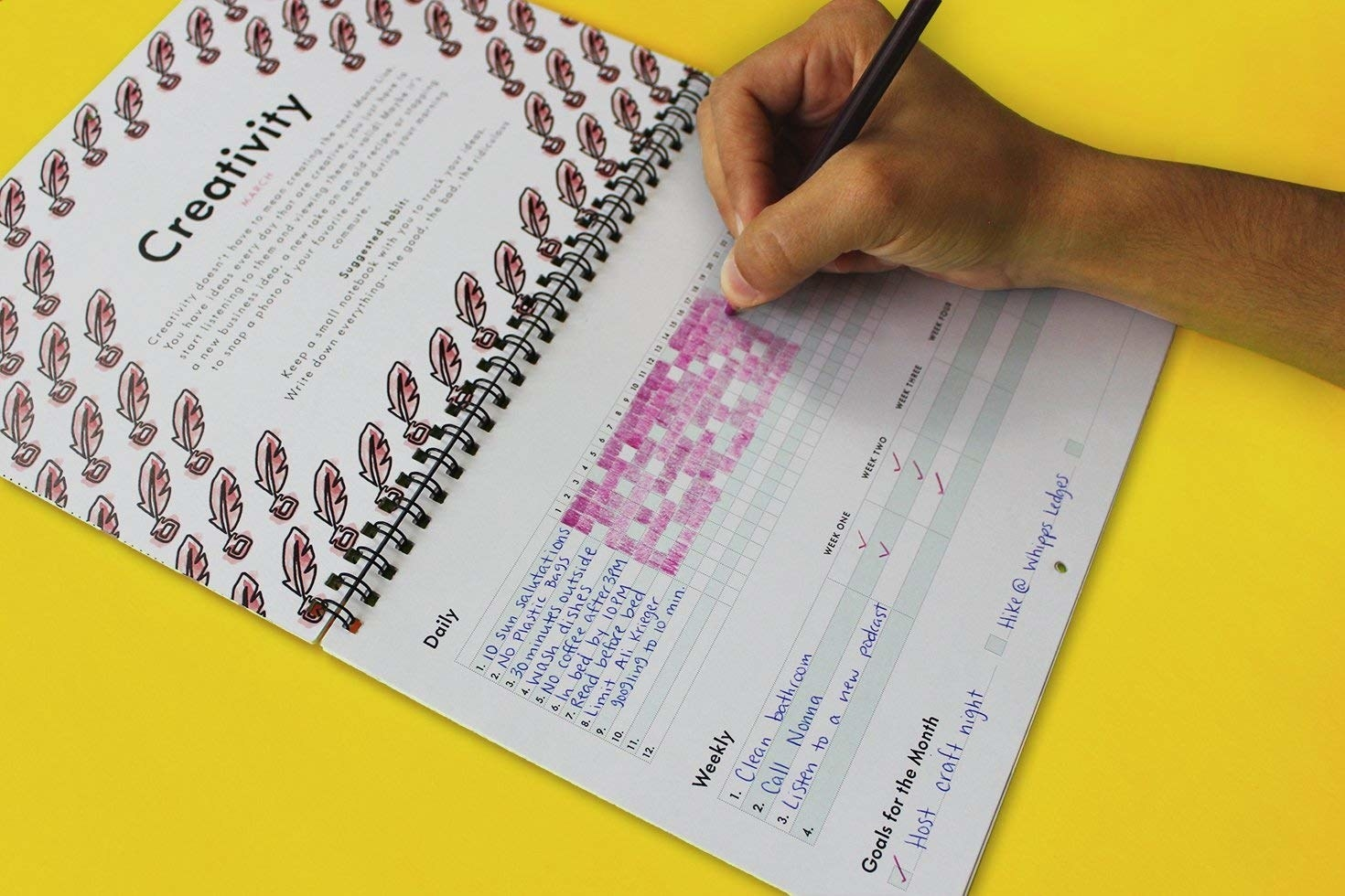 a hand filling out a habit calendar