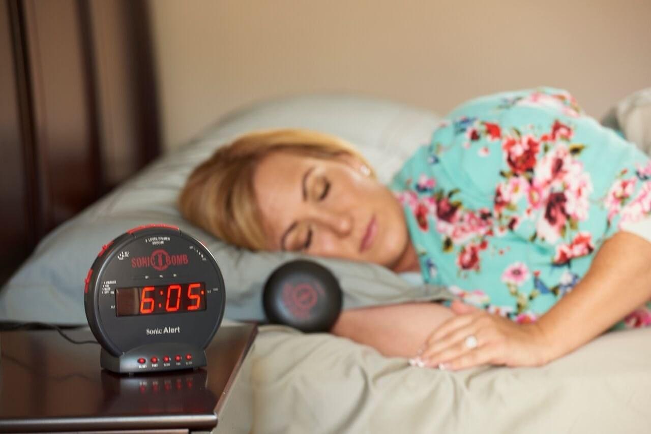a woman sleeping near an alarm clock