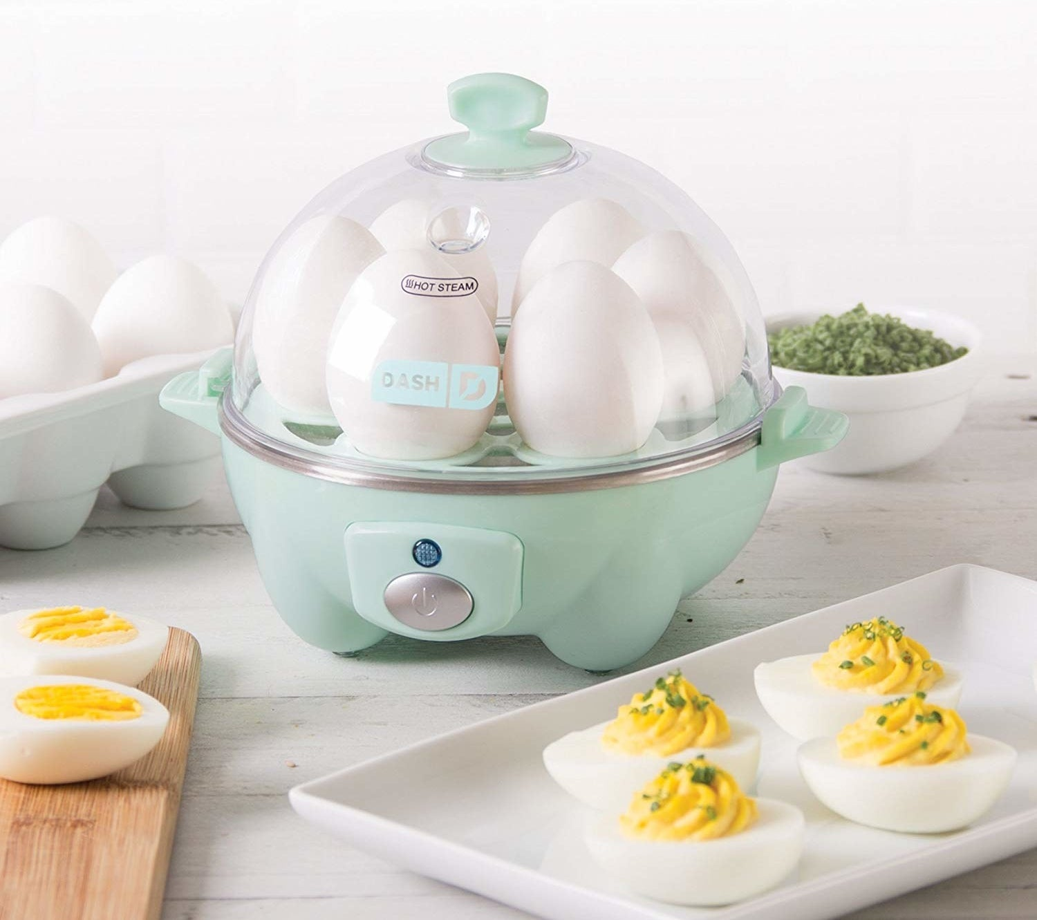 Dash rapid egg cooker placed on counter with deviled eggs on plate