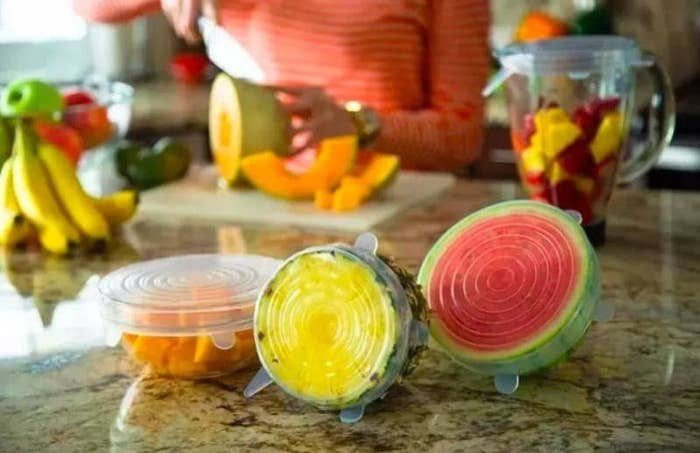 The silicone stretch lids covered over half a pinapple, half  watermelon, and a container of chopped fruit